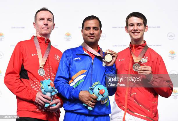 Silver medalist Grzegorz Sych of Canada gold medalist Sanjeev Rajput of India and bronze medalist Dean Bale of England pose after the Men's 50m Rifle...