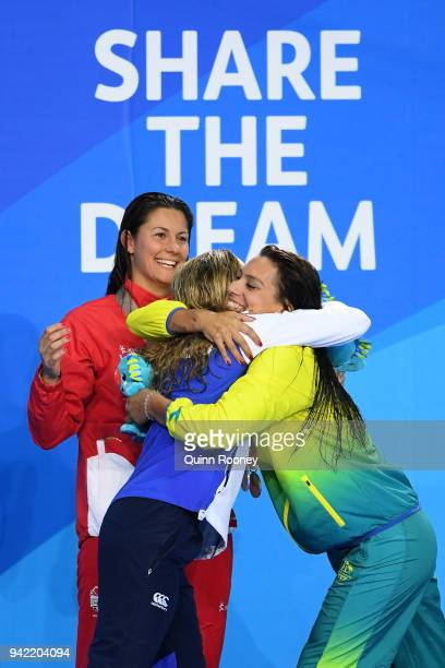 Silver medalist Hannah Miley of Scotland embraces bronze medalist Blair Evans of Australia as gold medalist Aimee Willmott looks on during the medal...