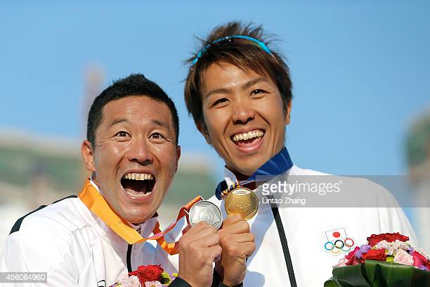 Silver medalist Hirokatsu Tayama and Gold medalist Yuichi Hosoda of Japan celebrate during the medal ceremony after the Triathlon Men's Final on day...