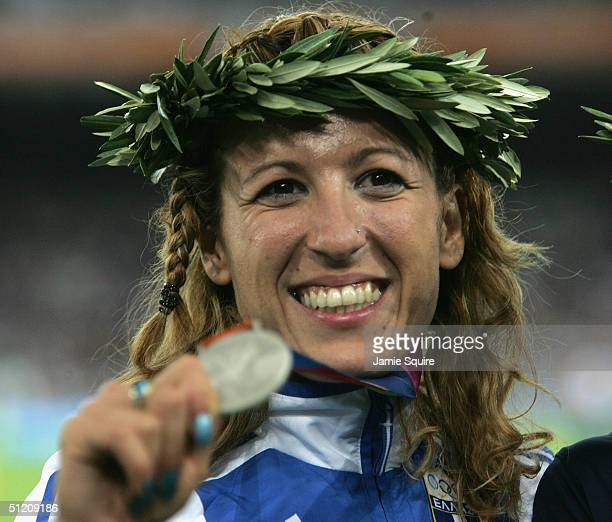Silver medalist Hrysopiyi Devezi of Greece celebrates on the podium during the medal ceremony of the women's triple jump event on August 23 2004...