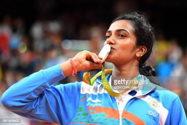 TOPSHOT Silver medalist India's Pusarla V Sindhu celebrates on the podium following the women's singles Gold Medal badminton match at the Riocentro...