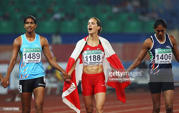 Silver medalist Jessica Zelinka of Canada celebrates with Susmita Singha Roy of India and Pramila Guddanda of India after the women's heptathlon at...