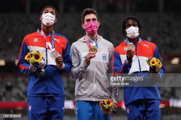 Silver medalist Juan Miguel Echevarria of Team Cuba, gold medalist Miltiadis Tentoglou of Team Greece and bronze medalist Maykel Masso of Team Cuba...