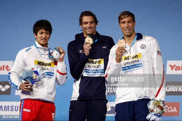 Silver medalist Junya Koga of Japan gold medalist Camille Lacourt of France and bronze medalist Matt Grevers of the United States pose with the...
