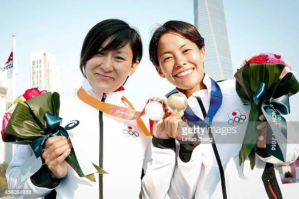 Silver medalist Juri Ide and Gold medalist Ai Ueda of Japan celebrate during the medal ceremony after the Triathlon Women's Final on day six of the...