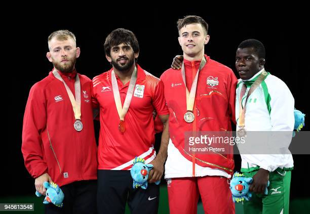 Silver medalist Kane Charig of Wales gold medalist Bajrang of India and bronze medalists Charlie Bowling of England and Amas Daniel of Nigeria pose...