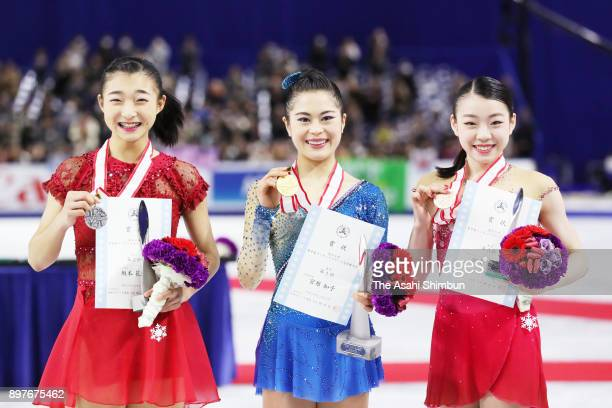 Silver medalist Kaori Sakamoto gold medalist Satoko Miyahara and bronze medalist Rika Kihira pose on the podium at the medal ceremony for the ladies...