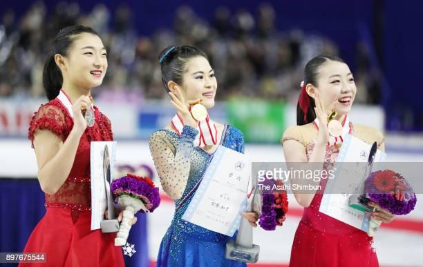 Silver medalist Kaori Sakamoto gold medalist Satoko Miyahara and bronze medalist Rika Kihira pose on the podium at the medal ceremony for the ladies...