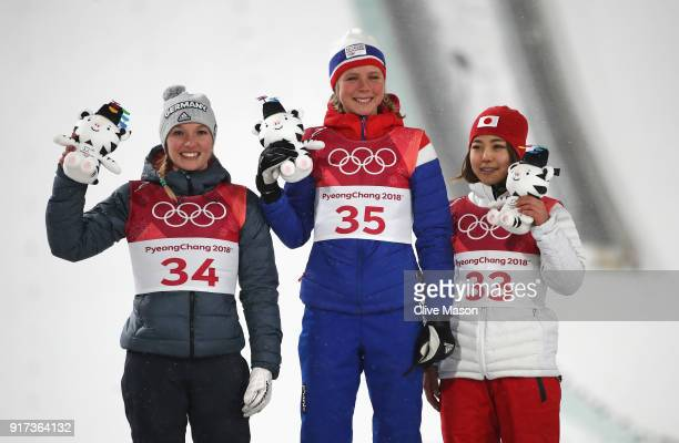 Silver medalist Katharina Althaus of Germany gold medalist Maren Lundby of Norway and bronze medalist Sara Takanashi of Japan stand on the podium...