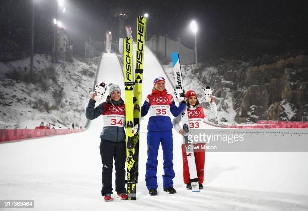 Silver medalist Katharina Althaus of Germany gold medalist Maren Lundby of Norway and bronze medalist Sara Takanashi of Japan celebrate after the...