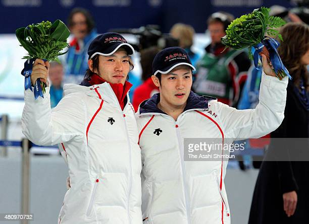 Silver medalist Keiichiro Nagashima and bronze medalist Joji Kato of Japan pose for photographs on the podium at the flower ceremony for the Speed...