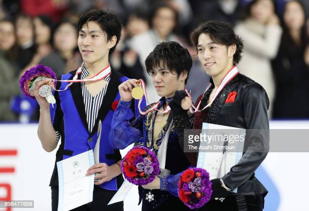 Silver medalist Keiji Tanaka gold medalist Shoma Uno and bronze medalist Takahito Mura pose for photographs on the podium at the medal ceremony for...