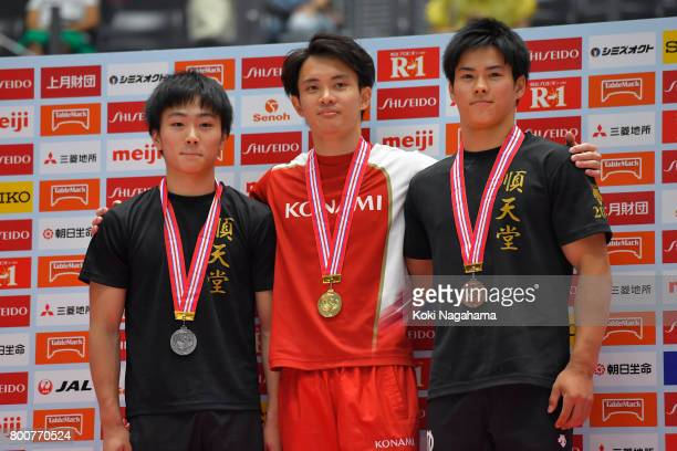 Silver medalist Kenta Chiba Gold medalist Yusuke Tanaka and Bronze medalist Kenya Yuasa pose for photographs in the award ceremony for the Parallel...