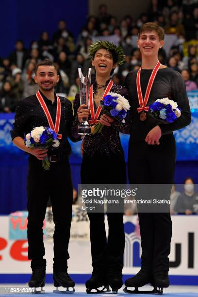 Silver medalist Kevin Aymoz of France, Gold medalist Yuzuru Hanyu of Japan and Bronze medalist Roman Sadovsky of Canada pose for photographs on the...