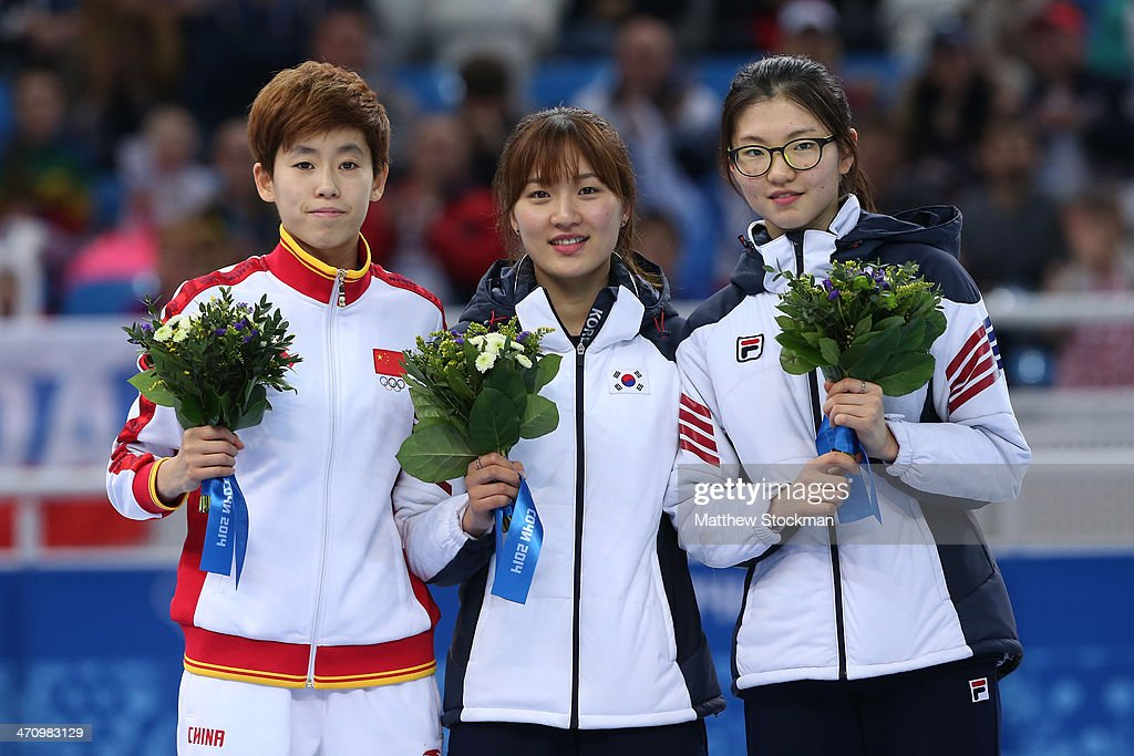 Silver medalist Kexin Fan of China, gold medalist Seung-Hi Park of South Korea and bronze medalist Suk Hee Shim of South Korea celebrate on the podium during the flower ceremony for the Short Track Women's 1000m on day fourteen of the 2014 Sochi Winter Olympics at Iceberg Skating Palace on February 21, 2014 in Sochi, Russia.