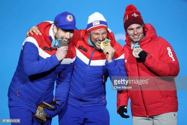 Silver medalist Kjetil Jansrud of Norway gold medalist Aksel Lund Svindal of Norway and bronze medalist Beat Feuz of Switzerland celebrate during the...