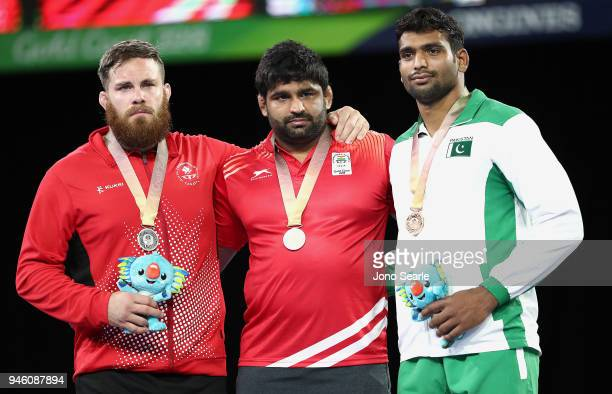 Silver Medalist Korey Jarvis of Canada gold medalist Sumit of India and bronze medalist Tayab Raza of Pakistan pose during the medal ceremony for the...