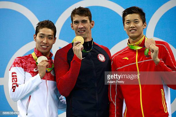Silver medalist Kosuke Hagino of Japan Gold medalist Michael Phelps of the United States and bronze medalist Shun Wang of China pose on the podium...