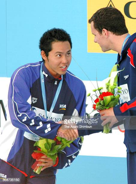 silver medalist Kosuke Kitajima of Japan shake hands with gold medalist Brendan Hansen of the United States on the podium at the medal ceremony for...