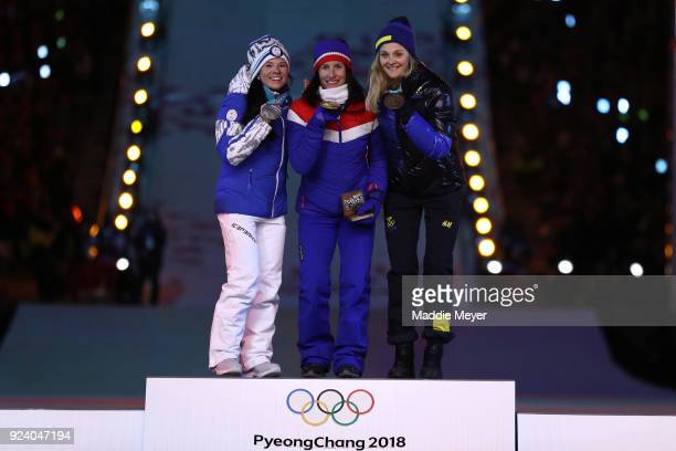 Silver medalist Krista Parmakoski of Finland gold medalist Marit Bjorgen of Norway and bronze medalist Stina Nilsson of Sweden poses during the medal...