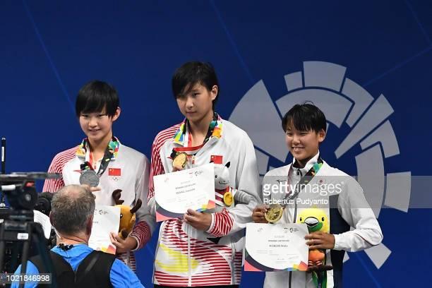 Silver medalist Li Bingjie of China gold medalist Jianjiahe Wang of China and bronze medalist Waka Kobori of Japan celebrate on the podium during...