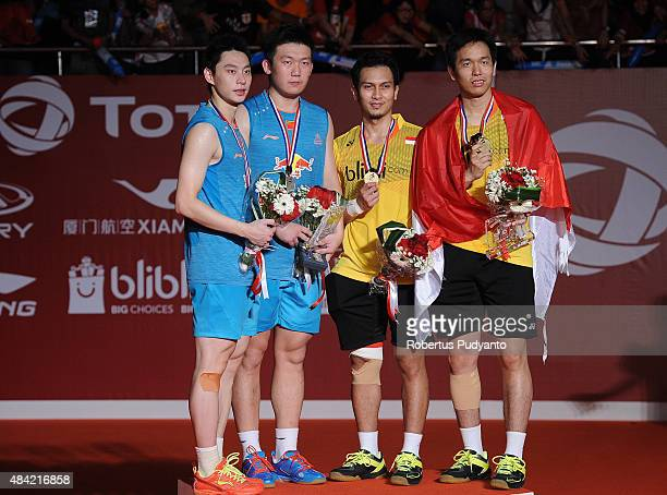 Silver medalist Liu Xiaolong and Qiu Zihan of China and gold medalist Mohammad Ahsan and Hendra Setiawan of Indonesia celebrate on the podium in the...