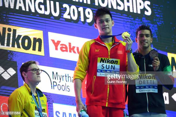 Silver medalist Mack Horton of Australia watches as gold medalist Sun Yang of China hold up his medal with bronze medalist Gabriele Detti of Italy...