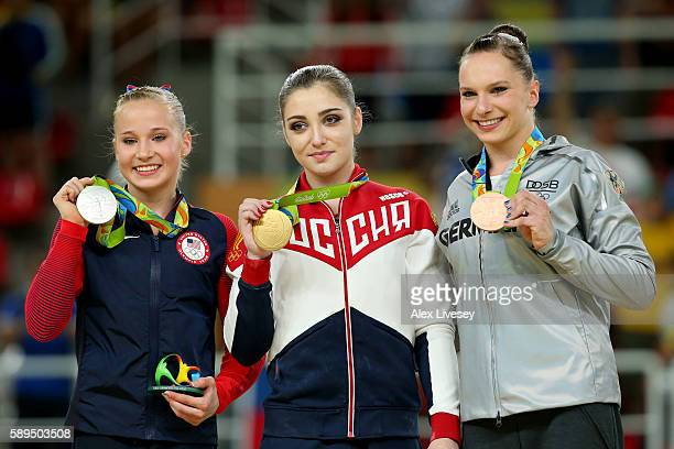 Silver medalist Madison Kocian of the United States gold medalist Aliya Mustafina of Russia and bronze medalist Sophie Scheder of Germany pose for...