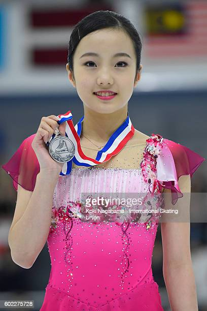 Silver medalist Marin Honda of Japan poses for photographs on the podium after the medal ceremony during the ISU Junior Grand Prix of Figure Skating...