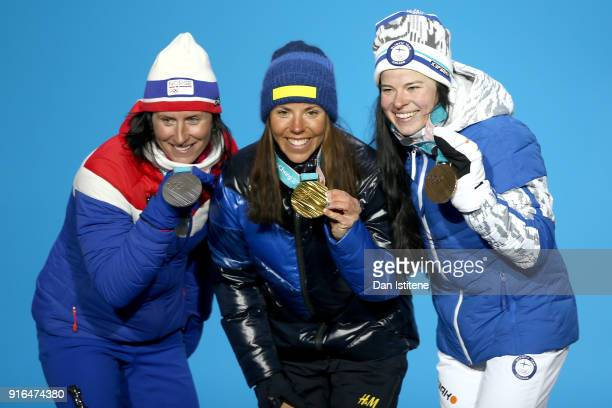 Silver medalist Marit Bjoergen of Norway gold medalist Charlotte Kalla of Sweden and bronze medalist Krista Parmakoski of Finland pose during the...