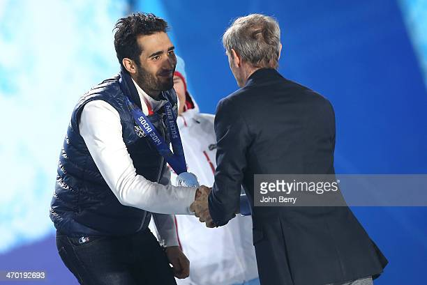 Silver medalist Martin Fourcade of France receives his medal from french Olympian JeanClaude Killy during the medal ceremony for the Men's 15 km Mass...