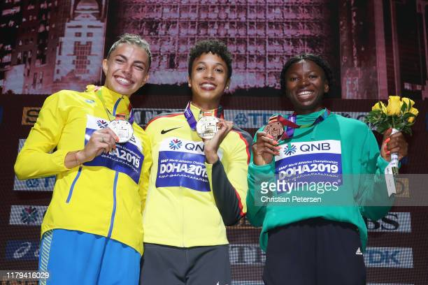 Silver medalist Maryna BekhRomanchuk of Ukraine gold medalist Malaika Mihambo of Germany and bronze medalist Ese Brume of Nigeria stand on the podium...