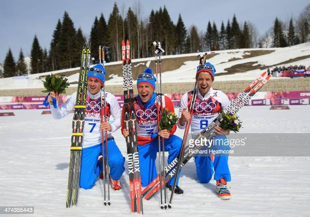 Silver medalist Maxim Vylegzhanin of Russia gold medalist Alexander Legkov of Russia and bronze medalist Ilia Chernousov of Russia celebrate during...