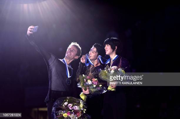 Silver medalist Michal Brezina of Czech Republic gold medalist Yuzuru Hanyu of Japan and bronze medalist Junhwan Cha of South Korea pose for a selfie...
