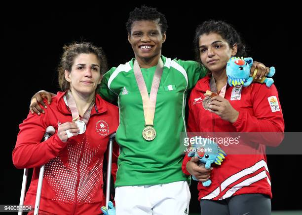 Silver Medalist Michelle Fazzari of Canada gold medalist Aminat Adeniyi of Nigeria and bronze medalist Malik Sakshi of India pose during the medal...