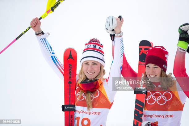 Silver medalist Mikaela Shiffrin of the United States and gold medal winner Michelle Gisin from Switzerland salute the crowd during the Alpine Skiing...