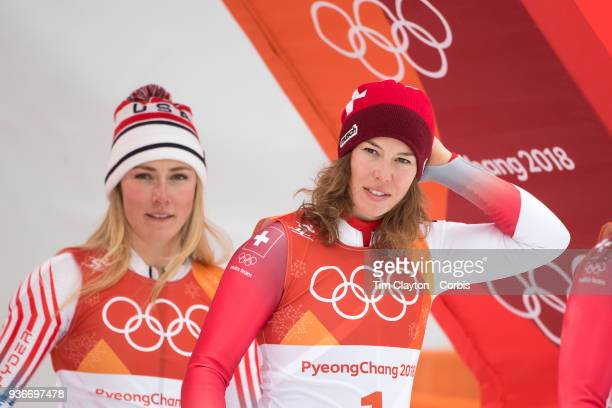 silver medalist Mikaela Shiffrin of the United States and gold medal winner Michelle Gisin from Switzerland head to the podium for presentations...