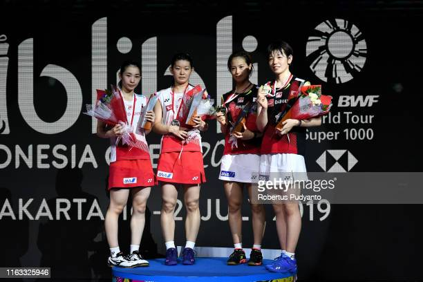 Silver medalist Misaki Matsutomo and Ayaka Takahashi of Japan and gold medalist Yuki Fukushima and Sayaka Hirota of Japan celebrate on the podium...