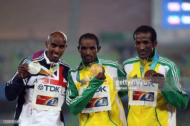 Silver medalist Mohamed Farah of Great Britain, gold medalist Ibrahim Jeilan of Ethiopia and bronze medalist Imane Merga celebrate on the podium with...