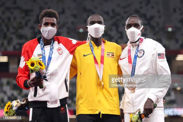 Silver medalist Mohammed Ahmed of Team Canada, gold medalist Joshua Cheptegei of Team Uganda, and bronze medalist Paul Chelimo of Team USA pose on...