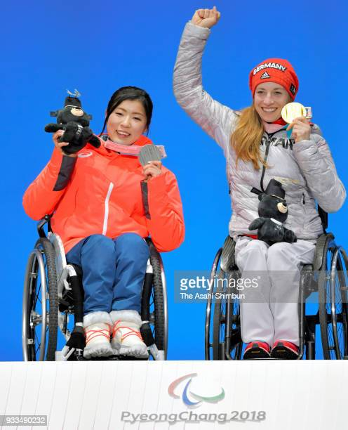 Silver medalist Momoka Muraoka of Japan and gold medalist Anna Schaffelhuber of Germany celebrate on the podium during the medal ceremony for the...