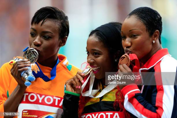 Silver medalist Murielle Ahoure of Ivory Coast, gold medalist Shelly-Ann Fraser-Pryce of Jamaica and bronze medalist Carmelita Jeter of the United...