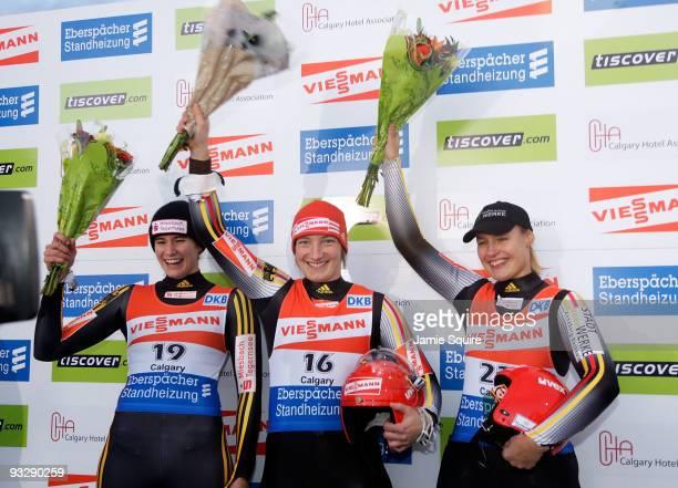 Silver medalist Natalie Geisenberger of Germany, gold medalist Tatjana Hufner of Germany, and bronze medalist Anke Wischnewski of Germany hoist...
