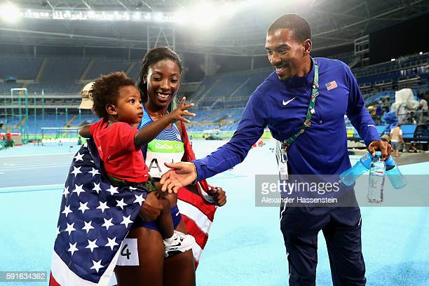 Silver medalist Nia Ali of the United States holds her son Titus as gold medalist Christian Taylor of the United States tries to shake his hand on...