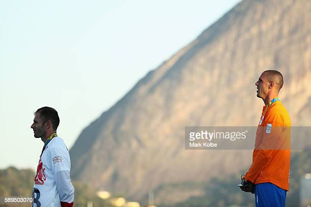 Silver medalist Nick Dempsey of Great Britain and gold medalist Dorian van Rijsselberghe of the Netherlands celebrate on the podium following the...