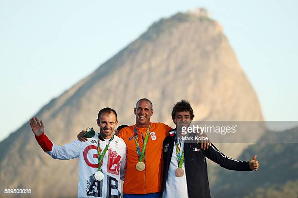 Silver medalist Nick Dempsey of Great Britain gold medalist Dorian van Rijsselberghe of the Netherlands and bronze medalist Pierre le Coq of France...