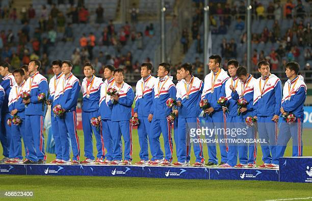 Silver medalist North Korea's team pose during the medal ceremony of the men's gold medal football match at Munhak Stadium during the 17th Asian...