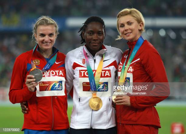 Silver medalist Olga Kucherenko of Russia, gold medalist Brittney Reese of United States and bronze medalist Ineta Radevica of Latvia celebrate on...