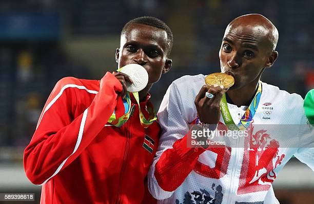 Silver medalist Paul Kipngetich Tanui of Kenya and Gold medalist Mohamed Farah of Great Britain celebrate on the podium during the medal ceremony for...