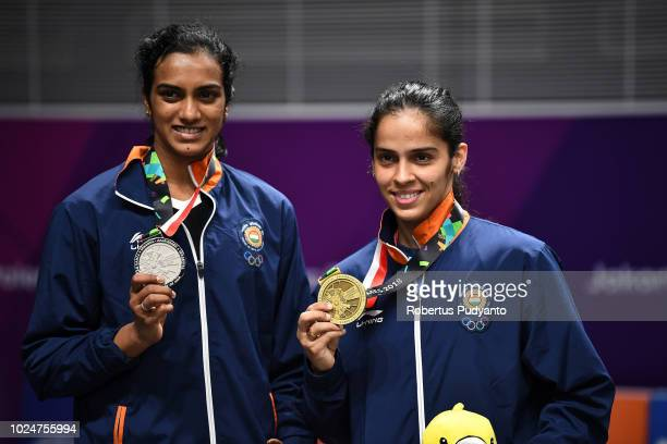 Silver medalist Pusarla V Sindhu of India and bronze medalist Saina Nehwal of India celebrate on the podium during Women's Singles medals ceremony on...